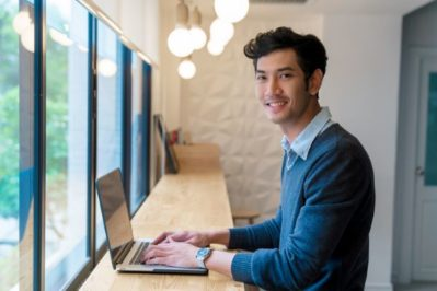 man working on laptop in front of window