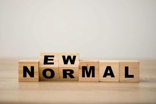 "wooden blocks flipping to spell ""new normal"""