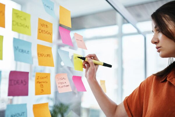 Young businesswoman brainstorming digital marketing ideas on multicolored notecards