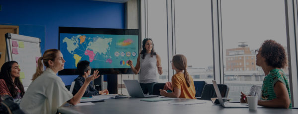 Woman leading a team meeting and pointing to a world map