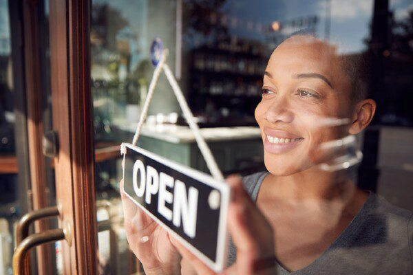 A small business owner opens her store for the day