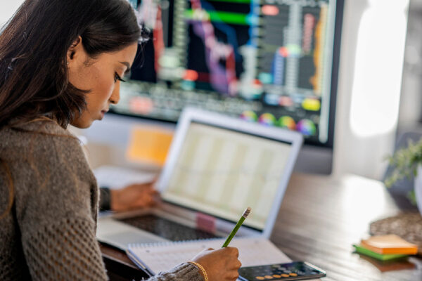 Women takes notes while looking at stocks and investments on a computer